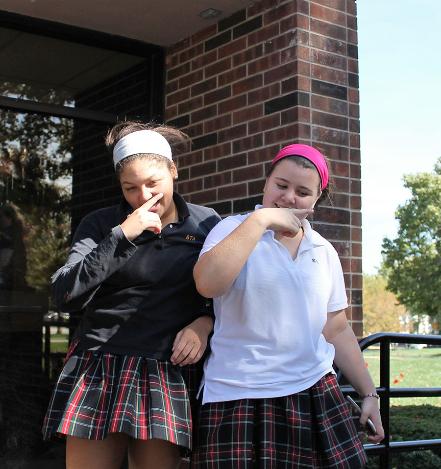Juniors Catelyn Campbell and Hayley Coleman dance in the quad at at St. Teresa's Academy on Oct. 17. Photo by Meghan Baker.