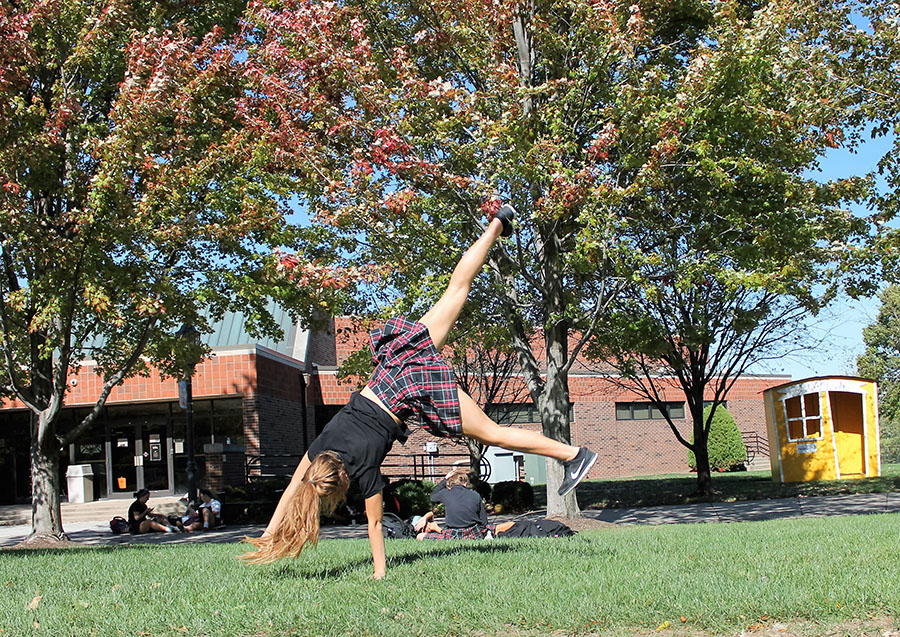 Junior Lulu Fiss cartwheels in the quad at St. Teresa's Academy on Oct. 17. Photo by Meghan Baker.