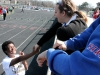 """Senior Serenity Wallace, left, and junior Jordan Berardi have a quick conversation before Serenity's event at the track invitational held at Bishop Miege High School April 5. """"€œI was about to run the hurdles and I told [Jordan] to hold my earrings,""""€ Wallace said. """"€œI got sixth place that day."""" by Viridiana Hernandez"""