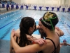 The 400 yard freestyle relay of senior Darby Pedersen, sophomore Maddie Adam, and juniors Molly Winkler and Libby Hutchinson huddle after their race. They were outtouched by the Notre Dame de Sion relay, getting second place by .07 seconds. photo by Mary Hilliard