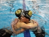 Junior Libby Hutchinson, left, hugs senior Darby Pedersen after getting her State cut in the 200 yard freestyle. Hutchinson won the event and Pedersen finished third. photo by Mary Hilliard