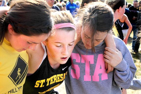 By Peyton Gajan. Juniors Sarah Vickery and Caitlin Fletcher help senior Lane Shulte after the race.