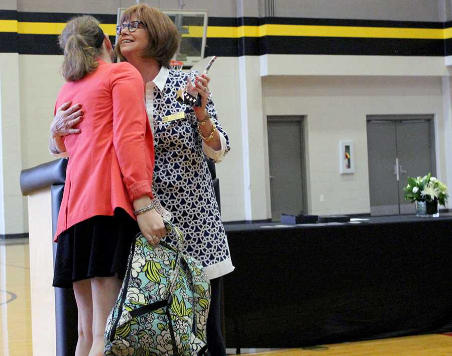 STA President Nan Bone congratulates senior Tricia Melland for wining the student Students clap for the student nominees at the Mother Evelyn O'Neill Service Award. photo by Bridget Jones.