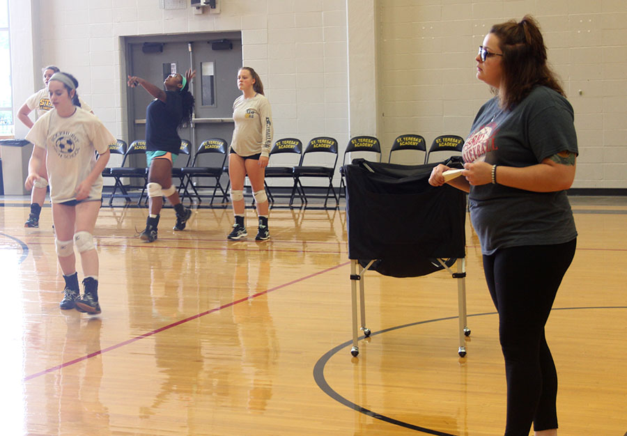 Sophomore coach Sami Sell watches as her team practices serving. photo by Paige Powell