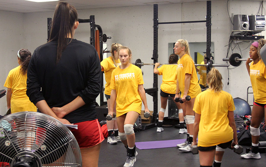 Volleyball coach Lauren Brentlinger instructs the varsity team in weight training Aug. 25. photo by Paige Powel
