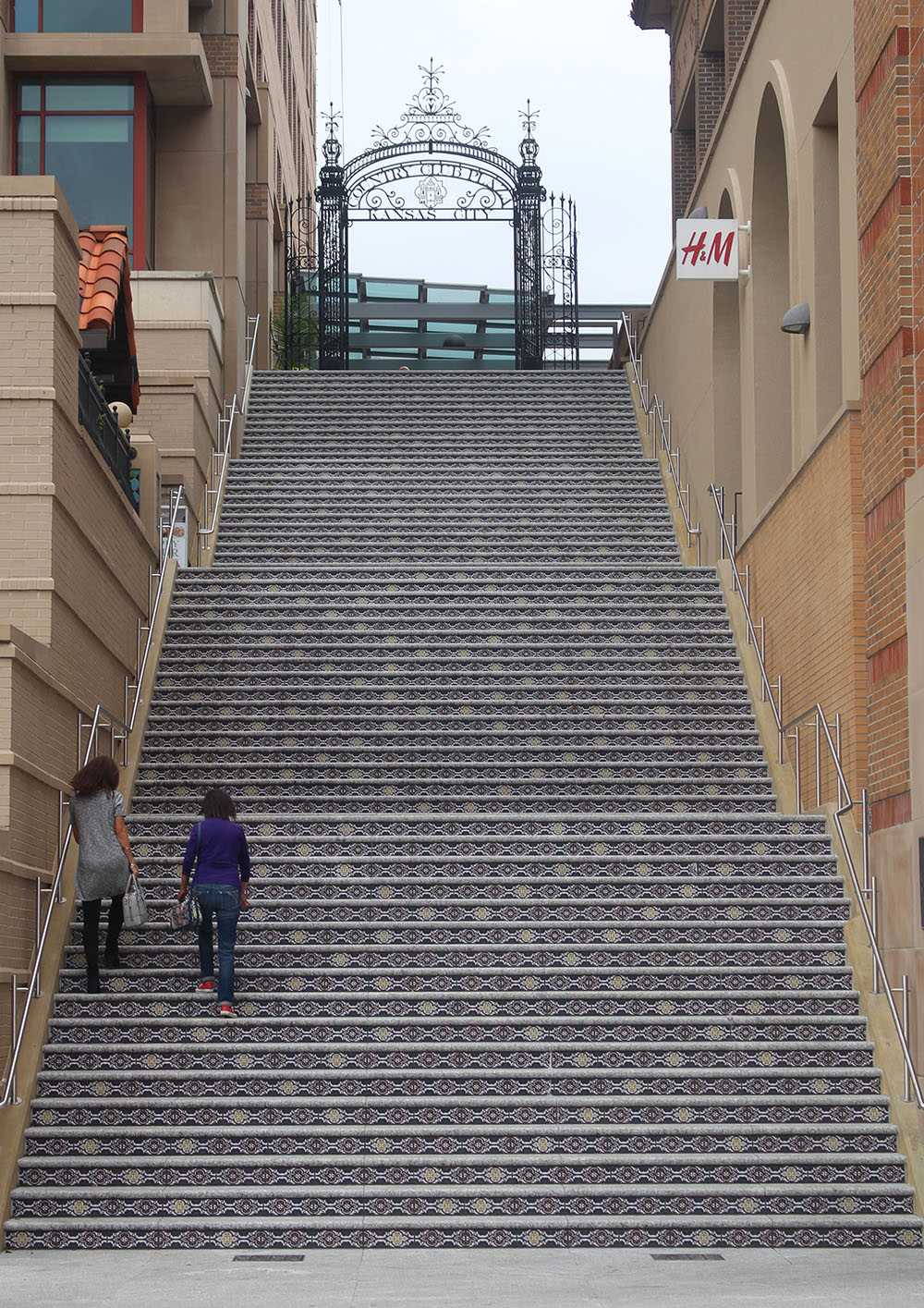 A mother and her daugher ascend a staircase leading up to a gate displaying a