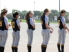 The varsity softball team claps for the St. Pius players as they line up before the National Anthem.