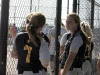 Sophomore Megan Klinginsmith, left, and junior Allison Bresette talk during the game in their dugout Sept. 18.