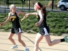 Sophomore Fee Pauwels passes the baton off to freshman Sophia Prochnow at the STA home meet on April 5. Pauwels and Prochnow are pole vaulters who decided to run a race for fun. by Giggy Reardon