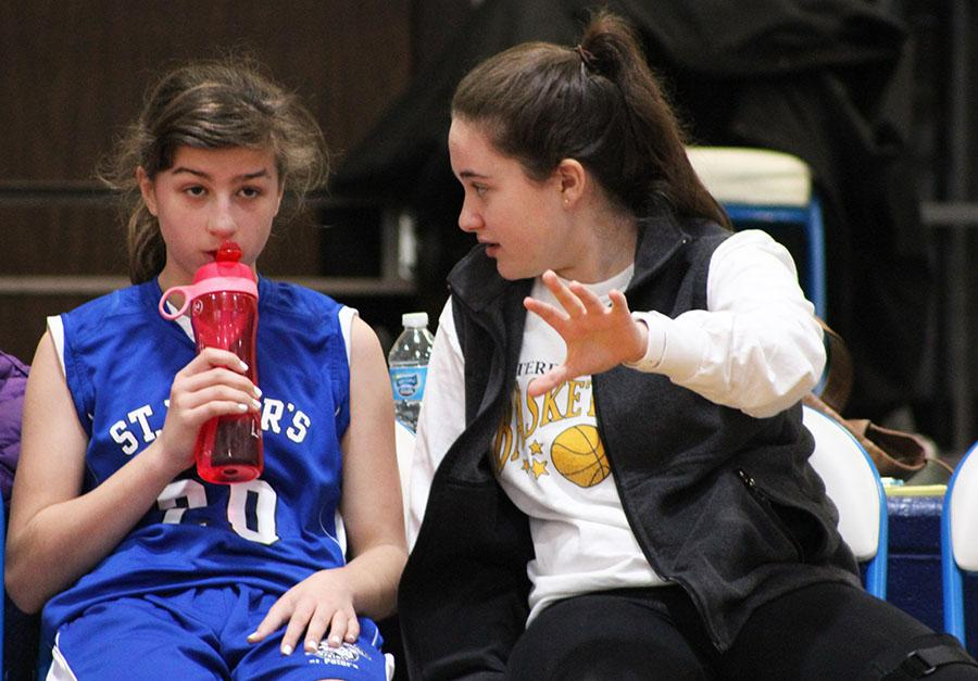 Senior Sophia Cusumano instructs St. Peter\'s seventh grader Molly Lombardi at St. James during the game Feb. 14. photo by Bridget Jones.
