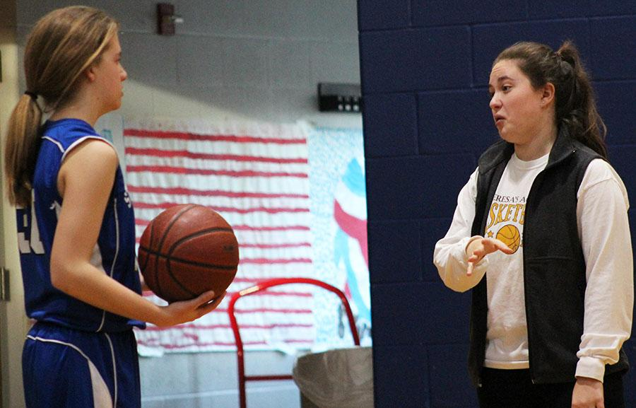 Senior Sophia Cusumano gives instructs St. Peter\'s seventh grader Georgia Winfield during halftime at St. James Feb. 14. photo by Bridget Jones.