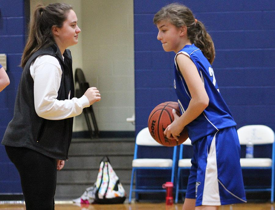 Senior Sophia Cusumano practices with St. Peter\'s seventh grader Molly Lombardi during halftime at St. James Feb. 14. photo by Bridget Jones.