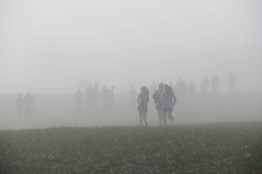 Members of the STA cross country team run to the start line at the Kearney meet Oct. 10. The morning of the race was foggy, but as the temperature rose the fog cleared. photo by Anna Hafner