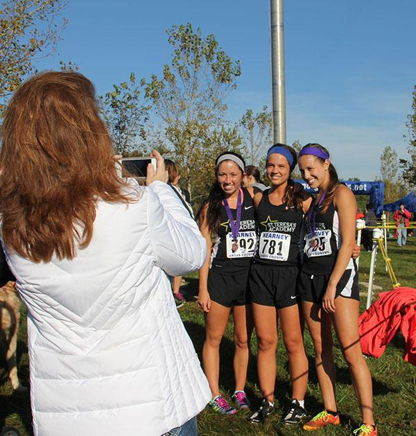 Cross country seniors McKenzie Burns, from left, Ellie Porterfield and Kara Black smile for a photo after their last meet in Kearney Oct. 10. photo by Anna Hafner