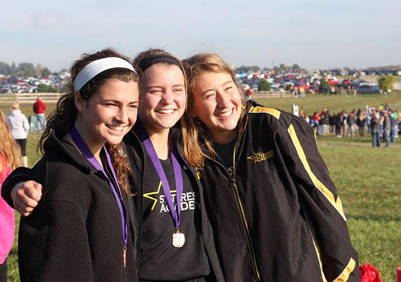Cross country senior captains Mary Hilliard, from left, Hallie Ryan and Emily Laird pose for a picture after running at the Kearney meet Oct. 10. photo by Anna Hafner