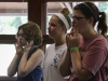 Sophomore Reilly Donnelly, from left, senior Molly Muehlebach and junior Courtney Talken warm up before singing at the STA Singers retreat Aug. 20. photo by Madi Winfield