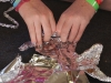"""Junior Kate Willnauer constructs a foil sculpture at the STA Singers retreat Aug. 21. Students were given the challenge to answer the question """"What can you bring to our choir?"""" out of tin foil. photo by Madi Winfield"""