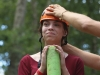 Sophomore Elise Cressey stands as a Trout Lodge employee sizes her ziplining helmet at the STA Singers retreat Aug. 20. photo by Madi Winfield