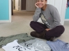 Senior Jewell Allen poses with a pile of her t-shirts. These shirts come in multiple designs and are handmade by both Jewell and her sister, STA alumna, Emma. photo by Kat Mediavilla