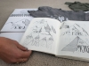 Senior Jewell Allen opens her sketchbook to her multiple designs for a