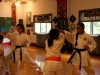 Sophomores Olivia Robertson, left, and Talia Parra practice with two younger students during their karate lesson. Having received their black belts, the girls now mainly focus on helping teach younger students during their lessons. photo by Gabby Martinez