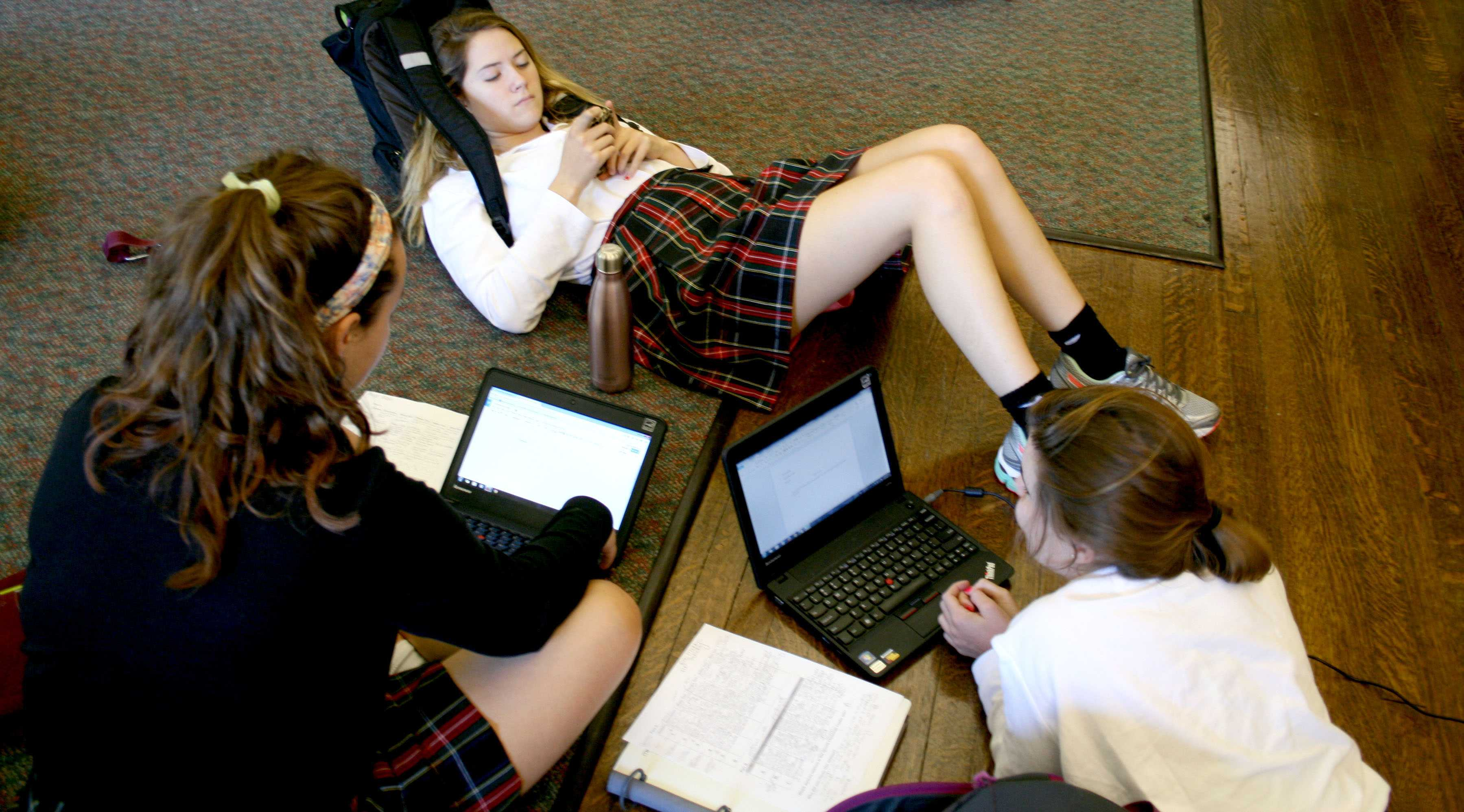 Juniors Rose Madden, Allie Mcdill and Anna Moore sit on their netbooks and phones during a free period in Mrs. Prentiss's room. photo by Kate Scofield