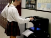 Junior Olivia Woodbury admires the new 3D printer in the third floor Donnelly hallway. The new printers are also located in Ms. Conner's room and the library. photo by Kate Scofield