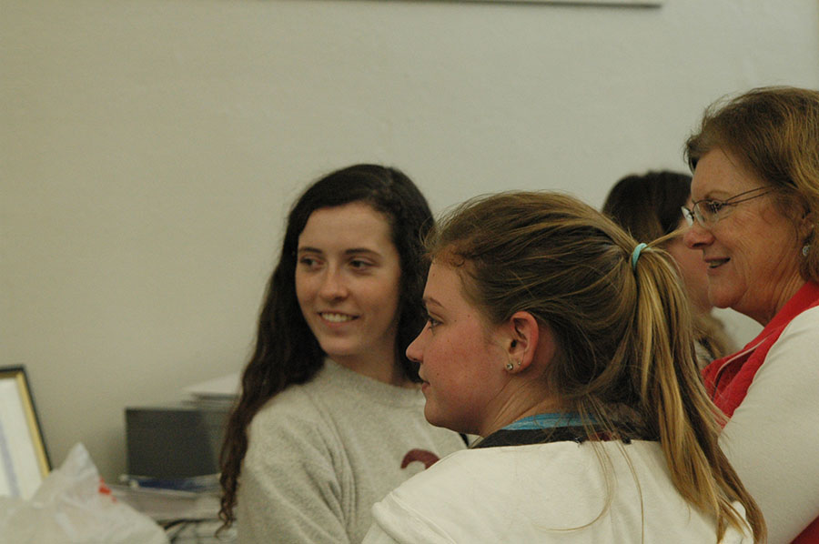 Alum Kellie O\'Toole, theology teacher Robin Good, and senior Sarah Cozad look towards the door as someone walks through. Cozad is apart of the Perry advisory which celebrated with Good advisory. photo by Riley McNett