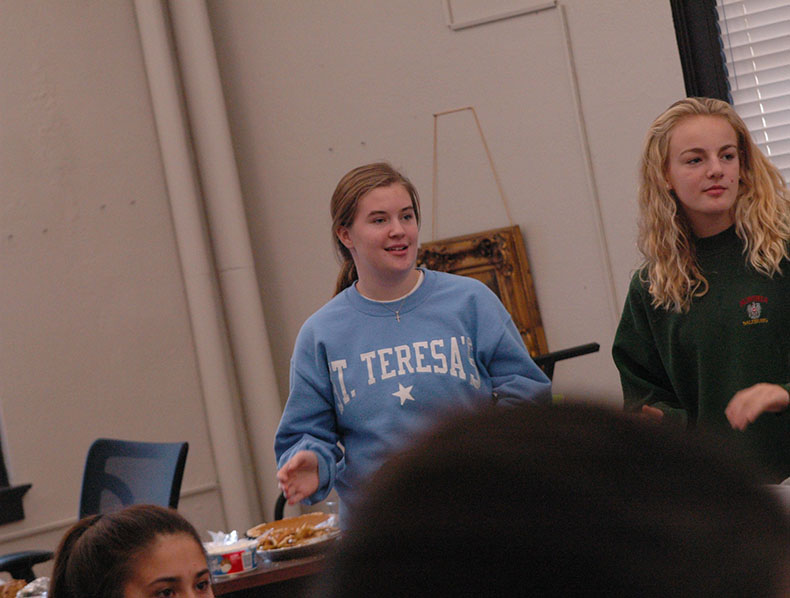 Freshmen Maggie Thompson and Kate Schaefer look at the rest of their advisory as they celebrate Thanksgiving. Thompson and Schaefer are members of the Perry advisory. photo by Riley McNett