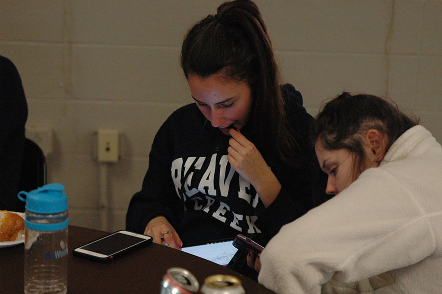 Freshmen Phoebe Burke and Olivia Heilman look down at Burke\'s computer as they wrap up celebrating Thanksgiving in advisory. Burke and Heilman are members of the O\'rear advisory. photo by Riley McNett