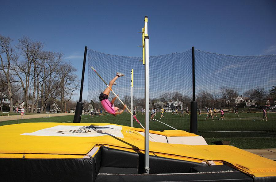 Senior Molly A. Mullen lands on the mat during the track team\'s varsity pole vaulting practice March 31. photo by Arinna Hoffine