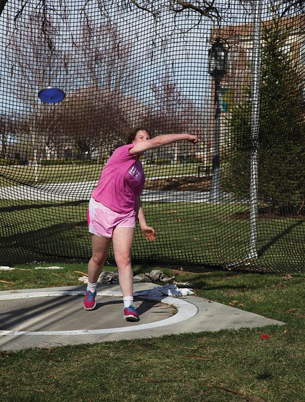 Sophomore Natalie Hull throws a discus from inside the ring. The throwing ring is surrounded by a very high net to protect surrounding people and property. photo by Arinna Hoffine