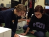 Community Service Club co-presidents Emily Laird, left, and Caitlin O'Toole help wrap boxes for