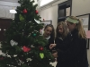 Freshmen Maggie Vasquez, from left, Kate Euston and Caroline Franke decorate a Christmas tree in the front hall of M&A Nov. 30.  photo by Anna Hafner