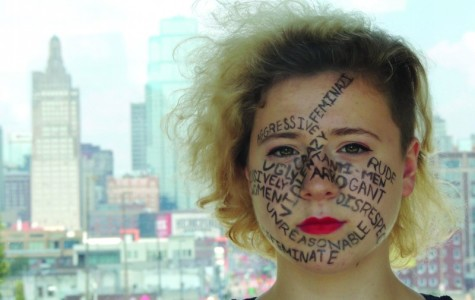 Junior Amber Brownlee sits in front of a view of downtown Kansas City with misconceptions of what feminists are written on her face Sept. 28.  photo by Maddy Medina