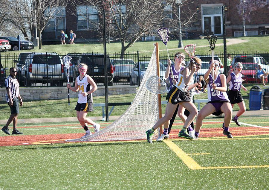 Senior+Jessica+Culver+sprints+past+Sion+defenders+Mar.+31+at+STA.+The+varsity+lacrosse+team+won+19-4.