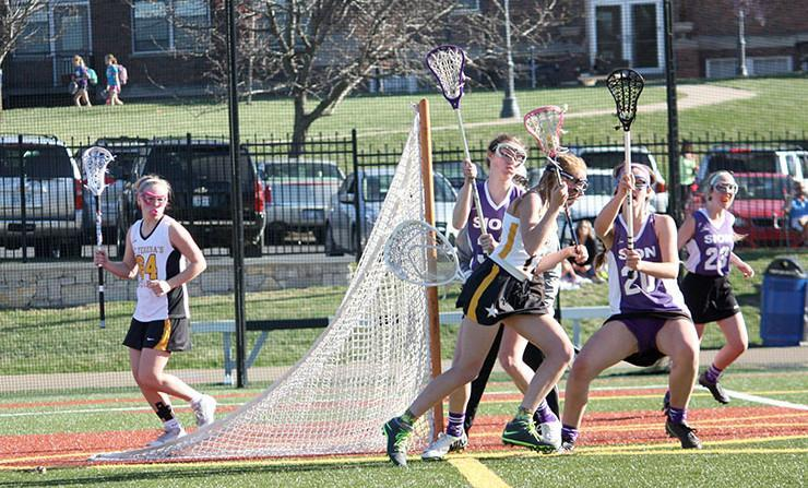 Senior Jessica Culver sprints past Sion defenders Mar. 31 at STA. The varsity lacrosse team won 19-4.