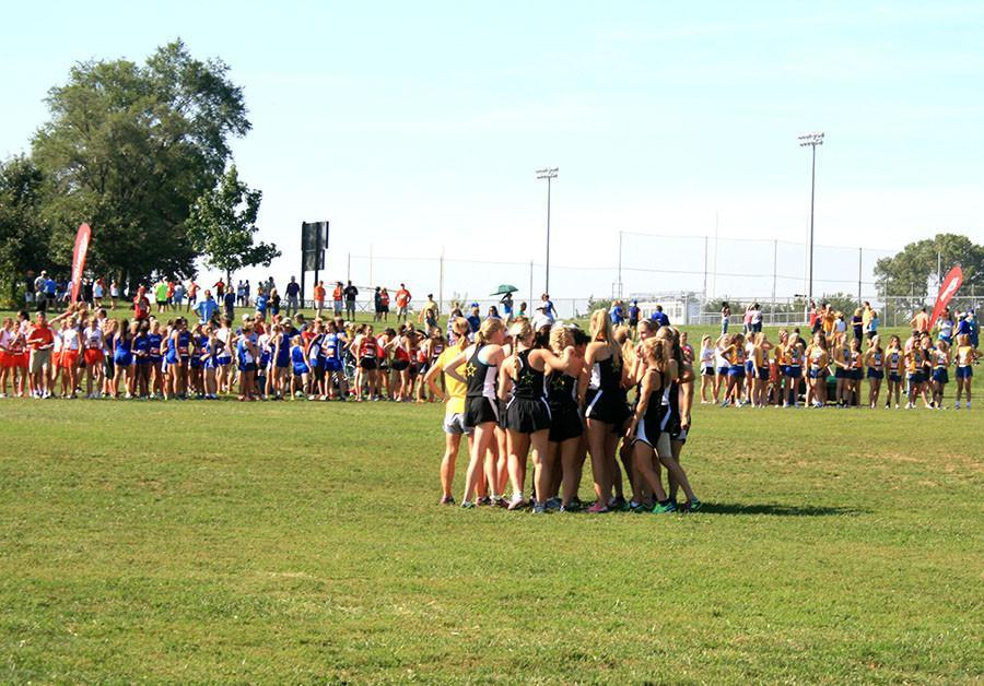 The cross country team huddles up before the start of the C-team race at the St. Thomas Aquinas Invitational on Sept. 5. photo by Kate Scofield