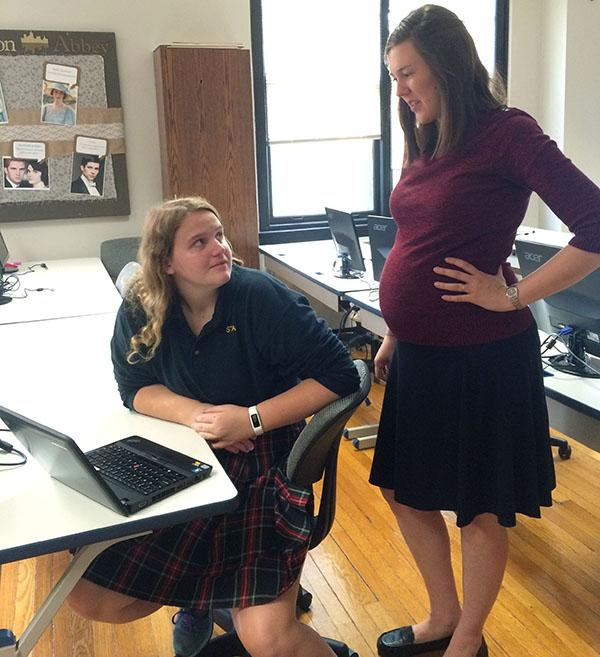 Kayla Leatherman helps senior Annie Alderman with her online personal finance class. Leatherman is six months pregnant. photo by Paige Powell