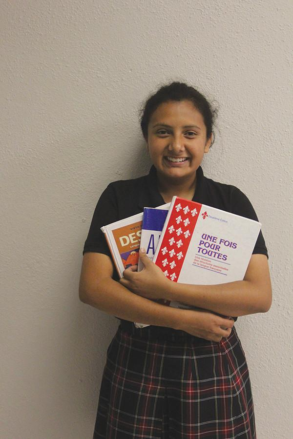 Sophomore Sarah Mendez smiles with language textbooks Sept. 28.  photo by Madi Winfield
