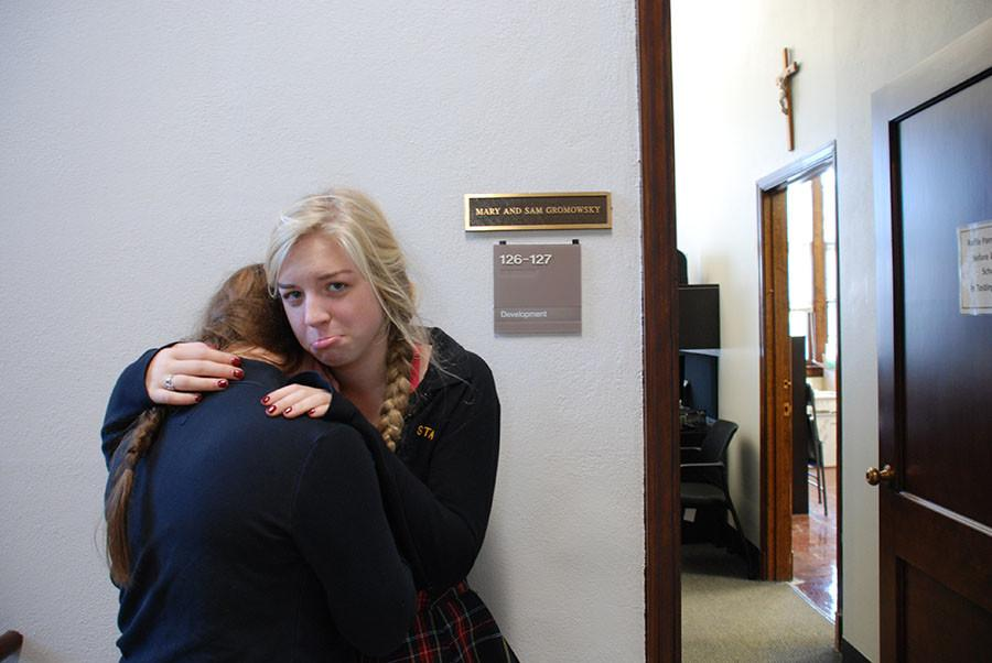 Juniors Laura Kieffer and Bailey Mitchell hug each other for support after learning candy will no longer be distributed from the development office. photo illustration by Elsa Feigenbaum