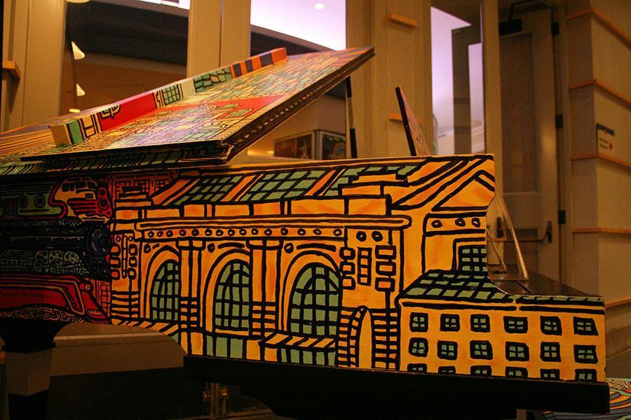 A piano, painted by local artist Charlie Podrebarac, sits in a gallery inside Union Station. Podrebarac's piano depicts several popular places in Kansas City, such as Union Station. photo by Cassie Hayes