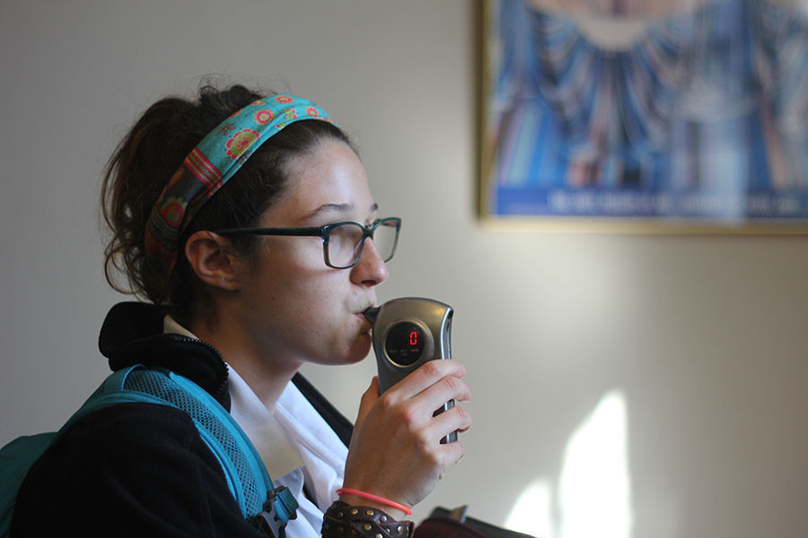 Junior Emma Kate Callahan practices blowing into STA's breathalyzer. The breathalyzer is stored in Baker's office and is present at all STA dances. photo illustration by Katie Donnellan