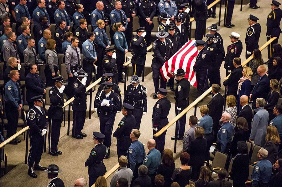 The Colorado Springs Police Honor Guard carries in the casket of Garrett Swasey, the 44-year-old University of Colorado at Colorado Springs police officer and six-year veteran of the department, during the funeral service at New Life Church on Friday, Dec. 4, 2015, in Colorado Springs, Colo. Swasey was killed Nov. 27 after responding to a shooting at a Colorado Springs Planned Parenthood, which left two others dead and 12 injured. (Stacie Scott/Colorado Springs Gazette/TNS) photo courtesy of MCT Campus