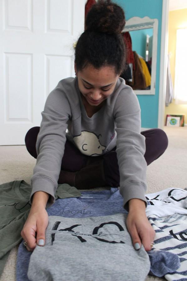 Senior Jewell Allen folds her t-shirts. Allen designs and sells these shirts with her sister. photo by Kat Mediavilla