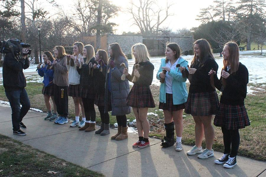 The ten STA students who cut their hair pose for Matt Kline, a Fox 4 news cameraman, at the Beautiful Lengths ceremony Jan. 5 at Loose Park. Kline worked with evening anchor Abby Eden to report on the event. photo by Maggie Knox