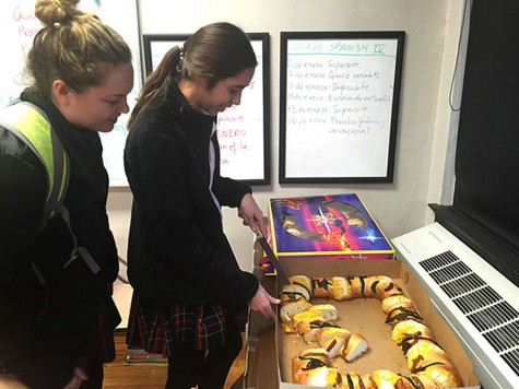 Junior Paige Powell watches Junior Isabella Solorio cut the King's Cake for their College Spanish III class. Spanish teacher Julia Gargallo asked Solorio to cut the dense, fruit-topped cake as Gargallo handed pieces to the incoming students. photo by Mackenzie O'Guin