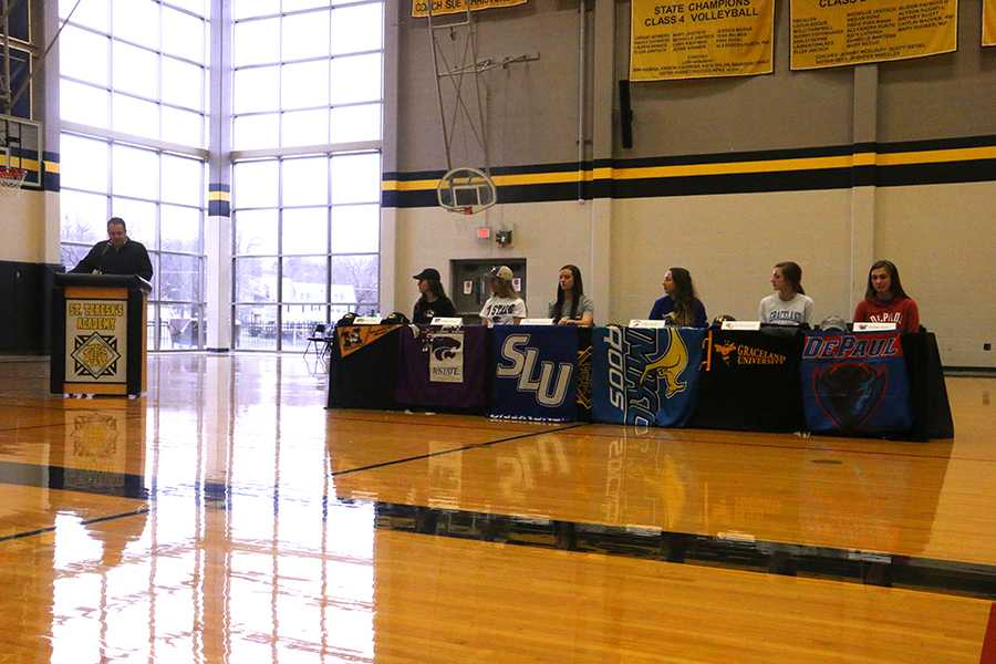 Athletic director Mark Hough, left, presents the six seniors signing National Letters of Intent Feb. 3. From left, seniors Grace Kitts, Maddy Russell, Alyssa Seitzer, Abby Small, Emma Runyan and Maddie Torti sit at the college sports signing ceremony. photo by Maggie Knox