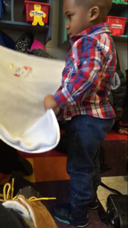 A kid at the Upper Room folds his blanket after nap time. photo courtesy of Molly Winkler