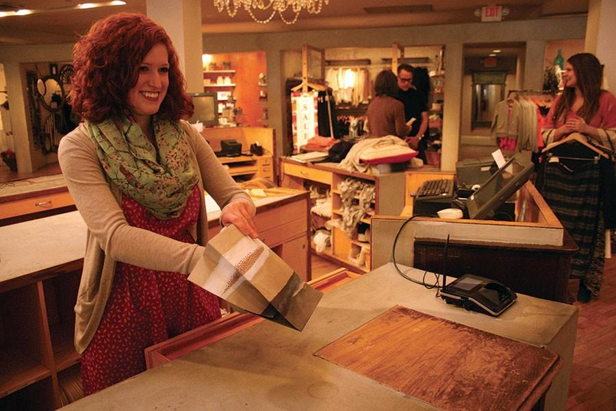 STA teacher Maura Lammers bags an item for a customer at her second job, Anthropologie. Lammers works at Anthropologie weekends and after school.